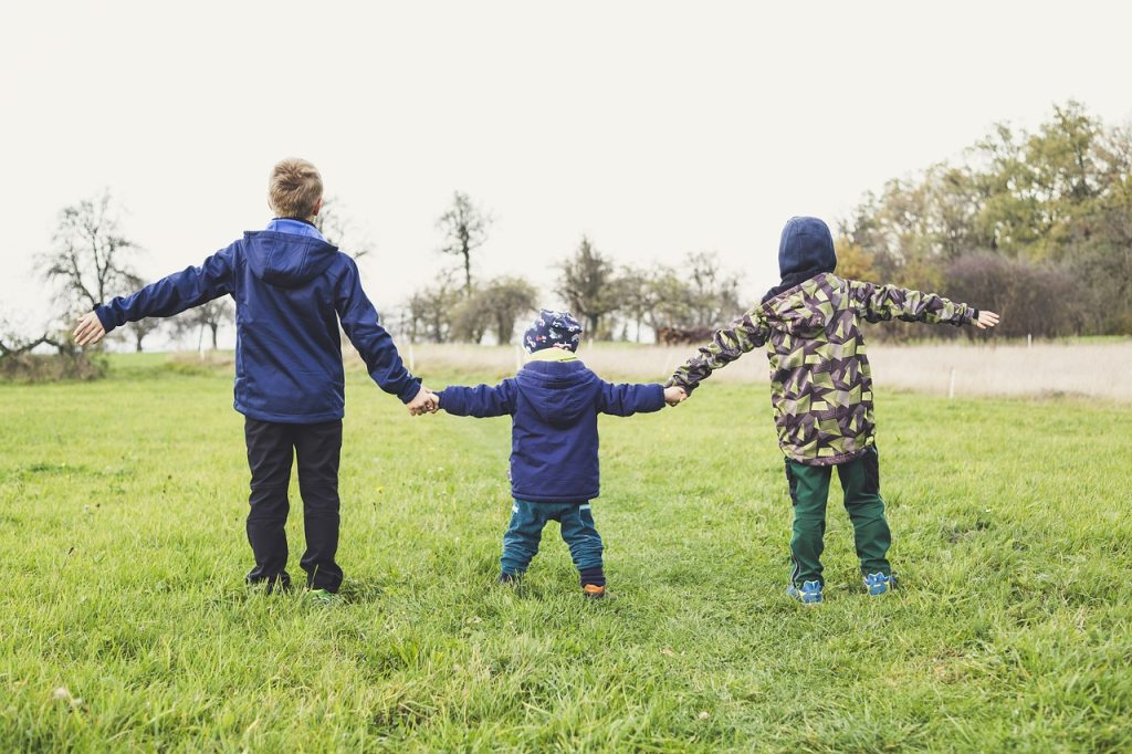three children holding hands